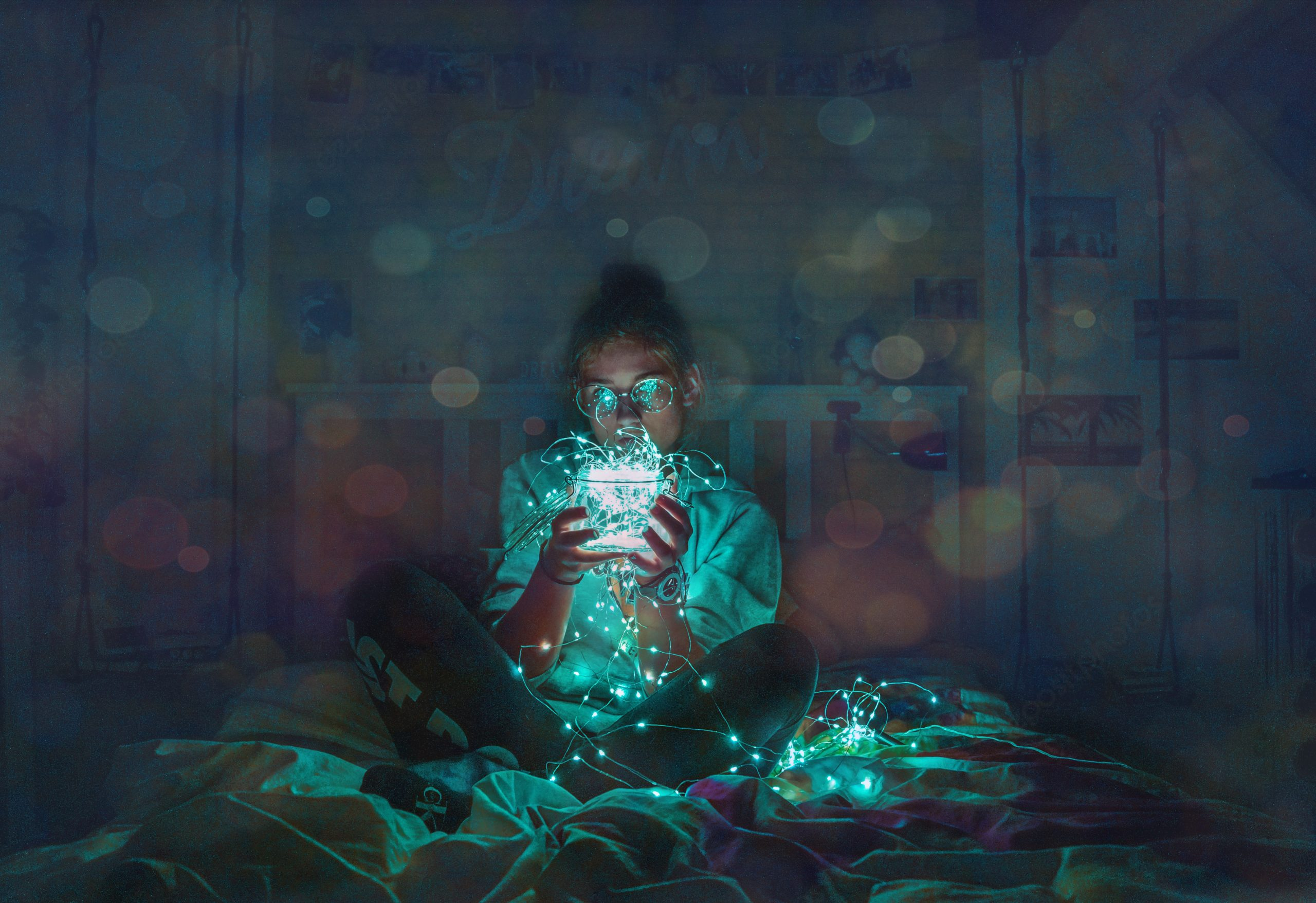 Electronics can disrupt an ADHD bedtime routine. person in bed using an electronic device, information is glowing all around them and lighting up the dark room